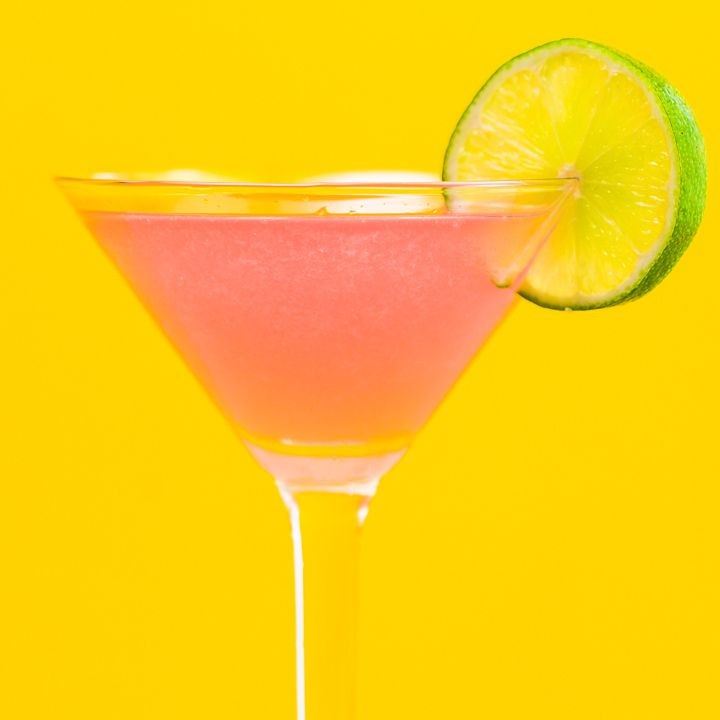 A vivid pink Cosmopolitan in a classic Martini glass is garnished with a whole lime wheel. The background is bright yellow
