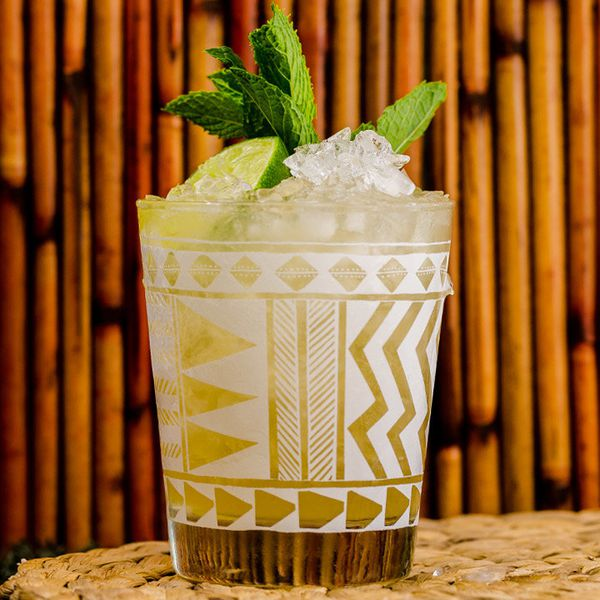 A Tiki glass with white markings holds a golden Mai Tai. Crushed ice, mint and a lime wedge pick from above the lip of the glass. The background is wood lines, and the drink rests on a wicker mat.
