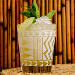 A short glass lined with white zig zagging designs is filled with crushed ice, a spring of mint, a thick slice of lime, and the golden hues of a Mai Tai