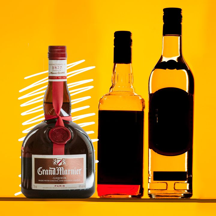 A stout Grand Marnier bottle sits on a yellow background. Next to it are other liquor bottles, their labels in shadow
