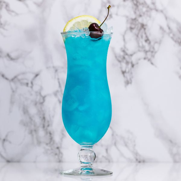 blue lagoon cocktail on a marble surface, garnished with a lemon and cherry