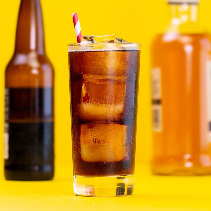 Bourbon and Root Beer cocktail on yellow surface with red-and-white straw