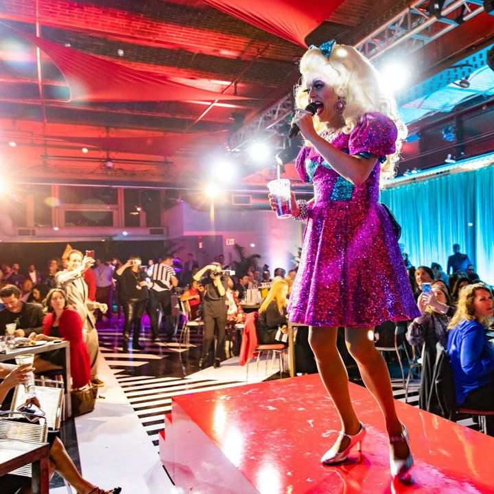 Razzle Dazzle on Virgin Voyages. a drag queen in a shint pink and blue dress entertains the crowd
