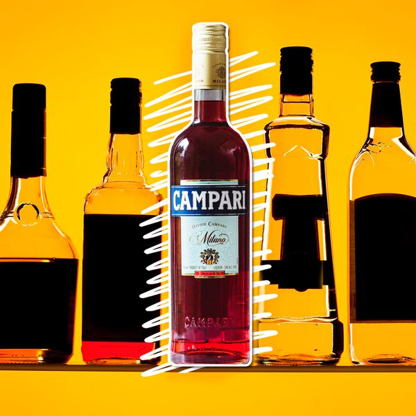 A bottle of ruby-hued Campari sits on a golden background. It is surrounded by other bottles, though their labels are darkened so as to be unreadable