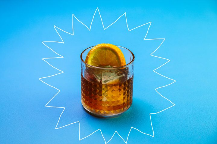 An Old Fashioned-style drink in a beveled rocks glass garnished with an orange wheel