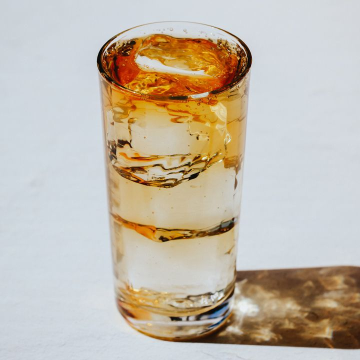 A Collins glass filled with clear ice cubes and an amber-hued effervescent drink