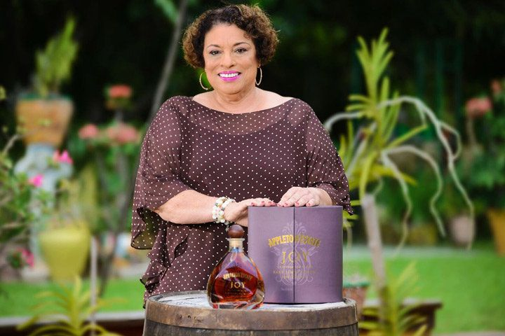A woman in a dark purple polka-dotted top stands smiling behind a bottle of Appleton Estate and its violet-hued box