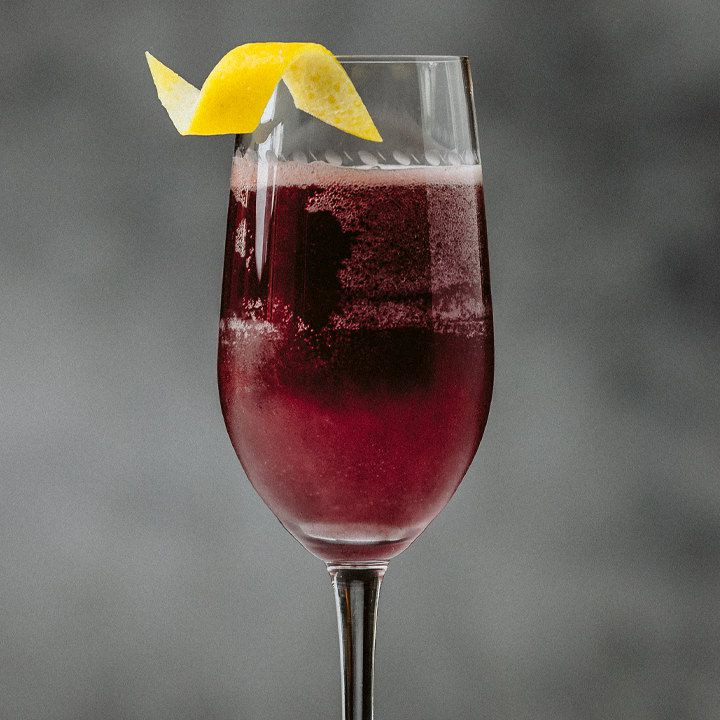The bowl of a champagne flute is shown in a close-up shot. It's filled with a bubbly violet drink and garnished with a small, curled lemon twist. The background is gray and fuzzy.