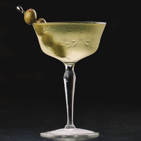 dirty martini cocktail with four skewered olives