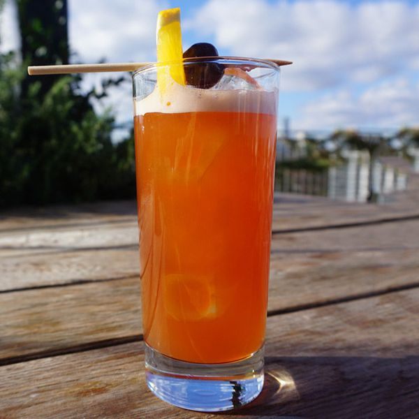 A red-orange Tiki cocktail served in a Collins glass, garnished with an orange slice and a brandied cherry on a wood pick