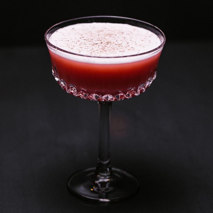 deep-red millionaire cocktail in a couple glass with grated nutmeg garnish