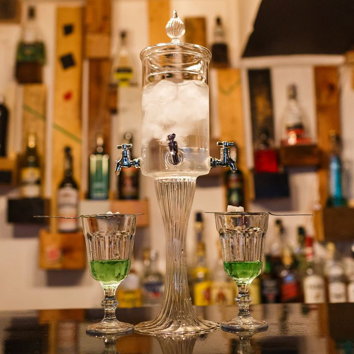 A dual-spouted absinthe fountain with two glasses
