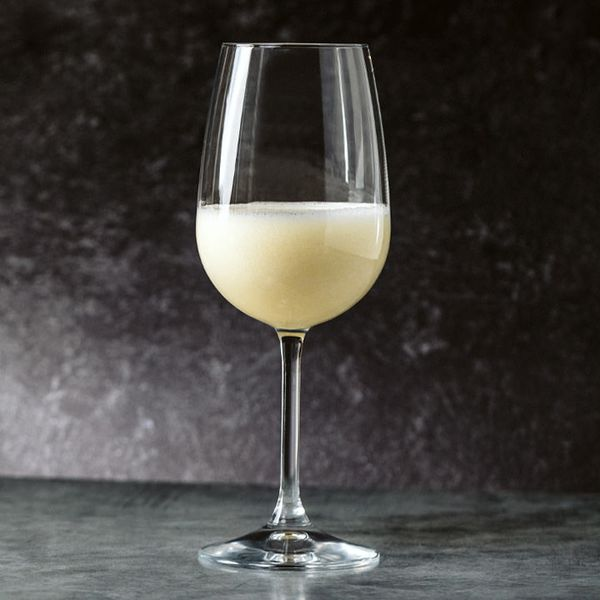 icy Sgroppino cocktail in a white wine glass set on a stone surface