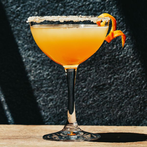 A curved martini glass rests on a wooden surface in front of a black stone wall. The glass is filled with an orange-colored cocktail and garnished with a spiral twist of orange. The rim is covered in sugar.