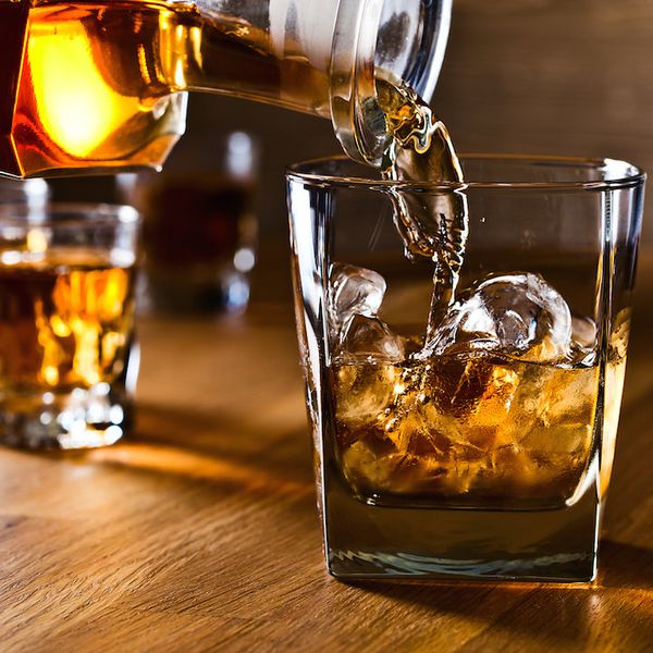 Pouring whiskey into a rocks glass with ice