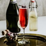 In the foreground, a champagne flute rests on a round metal tray. The drink within is bright red and bubbly, and the glass is garnished with two sugared cranberries on a skewer. Next to the drink is a small bowl of the same cranberries, and behind it is a bottle of champagne and a bottle of ginger beer. The background is a white floor and off-white wall.