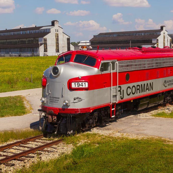 my old kentucky dinner train bourbon experience. a red and grey striped engine of a train in the foreground and distillery buildings in the background