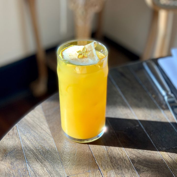 A golden yellow drink in a tall glass sits on a wooden table at Lou in Nashville. Topping the drink is a dried apple round, its center like a cut-out star