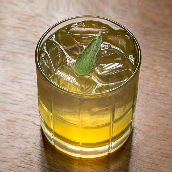 Switchel cocktail in a rocks glass garnished with a sage leaf