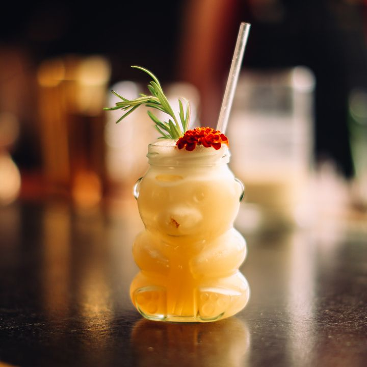A glass jar shaped like a honey bear sits on a reflective black bar top. It's filled with a honey-toned drink and garnished with an edible red flower and a sprig of rosemary. A clear plastic straw juts from the mouth of the jar.