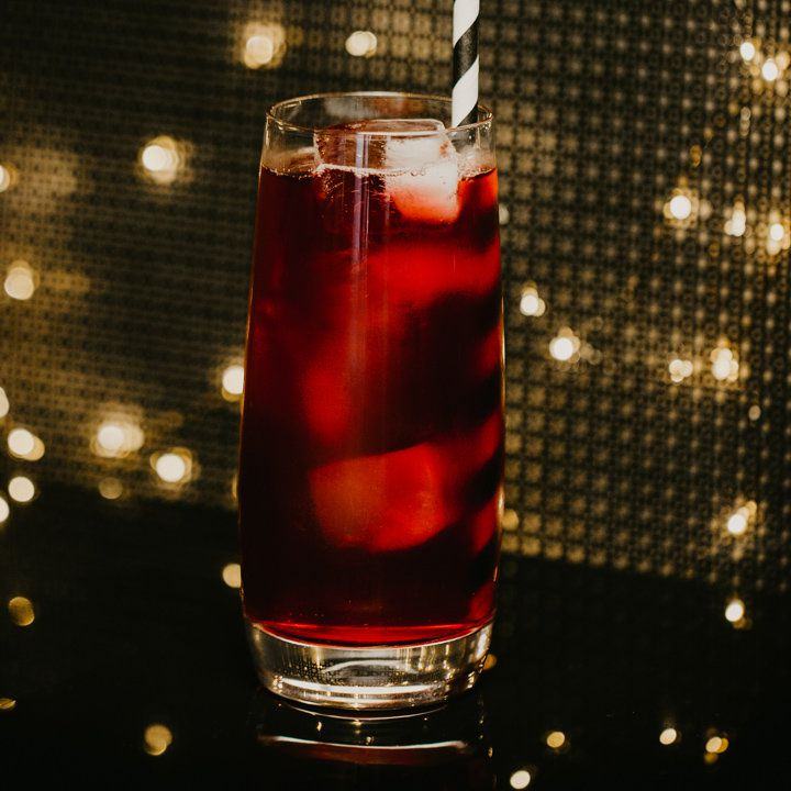 In a tapered Collins glass a few ice cubes float amongst a deep red tea. A black and white striped paper straw emerges from the the glass, and the background has a panel and glowing lights.