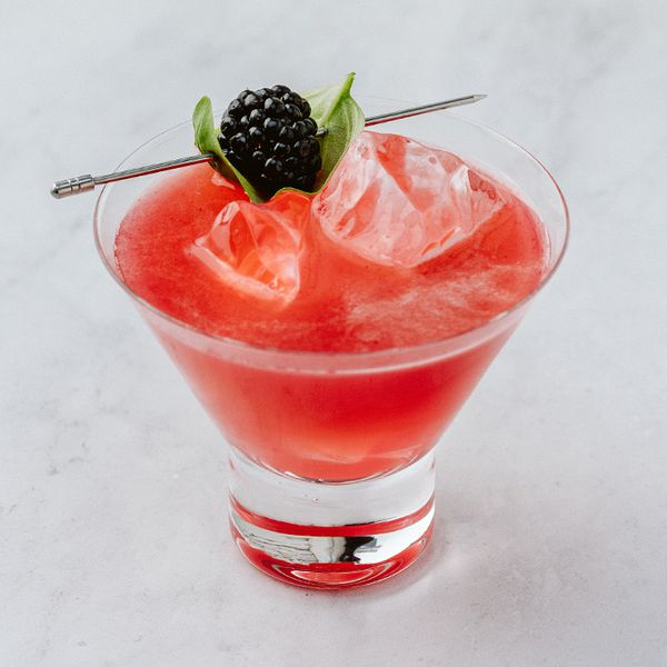 red-hued Black Widow cocktail in a stemless cocktail glass, garnished with skewered blackberry and basil leaf