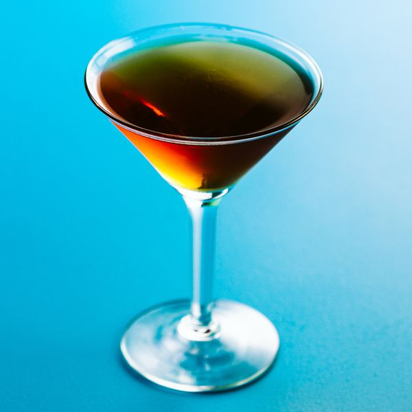chartreuse manhattan cocktail in a cocktail glass, served on a blue backdrop