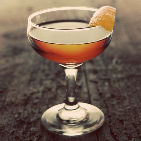 A coupe rests on a dark wood surface. It's filled with a golden drink and garnished with a slice of orange peel.