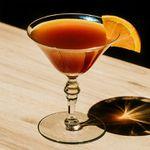 Orange Blossom cocktail with orange wedge garnish, served on wooden surface