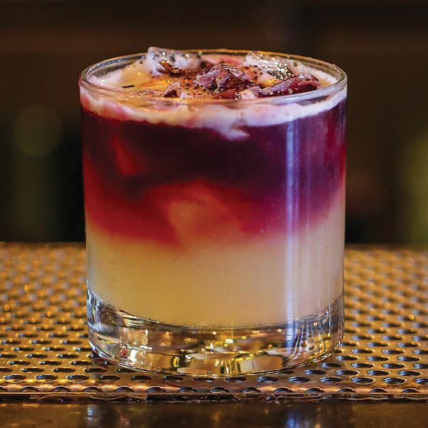 A short rocks glass rests on a bar top upon a perforated metal grate. The drink within is light gold and topped with a crimson wine that slowly gently with the drink. It's garnished with black pepper.