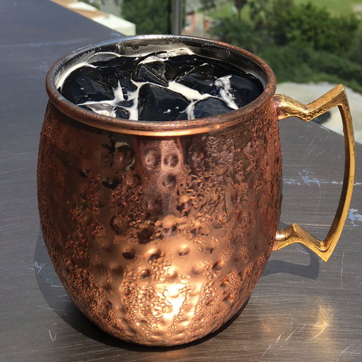 A faceted copper mug sitting on a metal bar top glistens with condensation. In it is a dark black drink over ice.