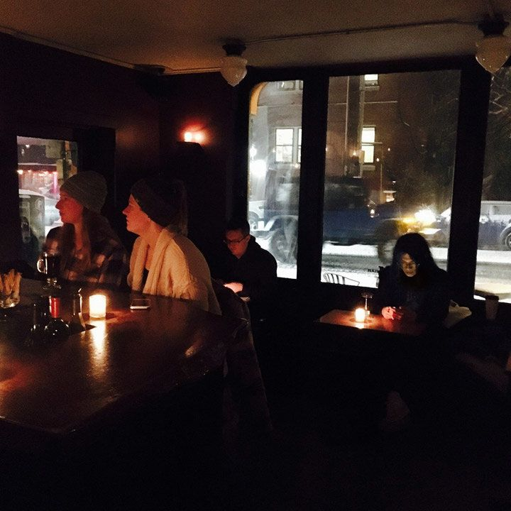 M Bar interior with guests, all lit by candlelight