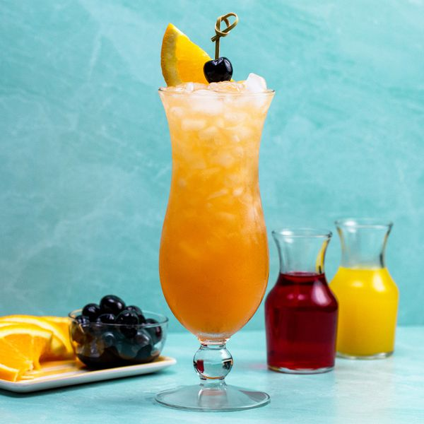 Hurricane cocktail on a light blue surface beside fresh fruit and juice carafes