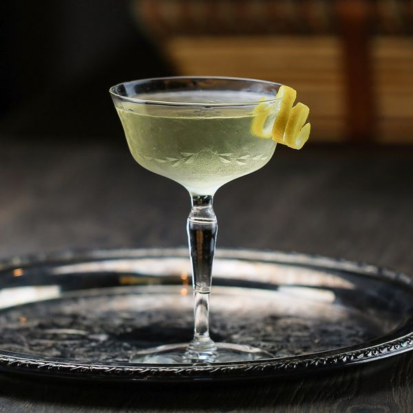 Coronation Cocktail No. 1 in a cocktail glass with a spiraled lemon twist, served on a round metal tray