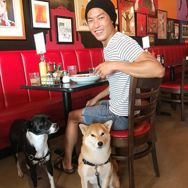 Norm's Eatery & Alehouse. a patron is looking at the camera and their two dogs are near his chair