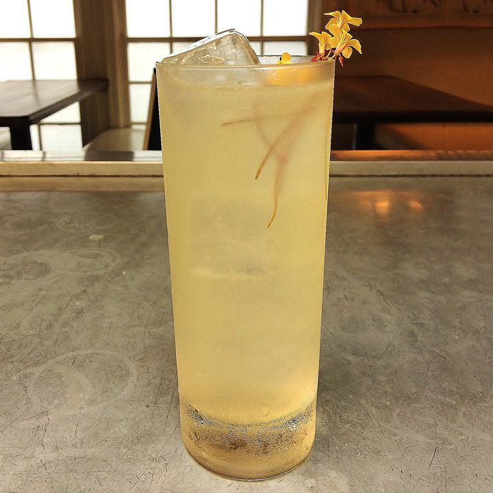 Pale Horse Rickey in a highball glass, served over ice and garnished with yellow edible flowers