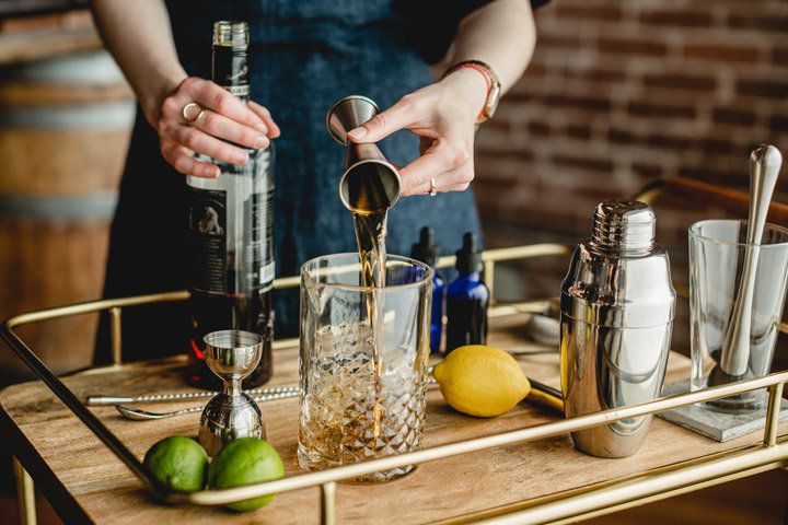 A bartender behind a wooden bar cart pours a brown spirit into a beveled mixing glass from a Japanese jigger