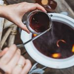 A pair of hands pour a steaming ladleful of mulled wine into a clear glass mug. The background with a crock pot full of mulled wine is just out of focus.