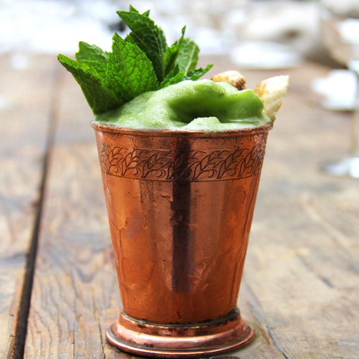 green-hued, slushy Miamian's Julep cocktail in a copper julep mug with mint garnish, served on a wooden table