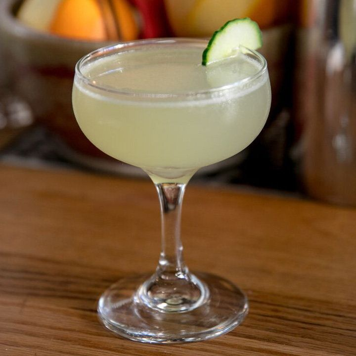 A coupe rests on a wooden surface, with a bowl of fruit out of focus in the background. The glass is filled with a pale green drink and garnished with a thin slice of cucumber.