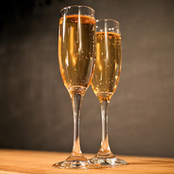 Two Champagne flutes are filled with a golden sparkling drink, set against a brown backdrop.