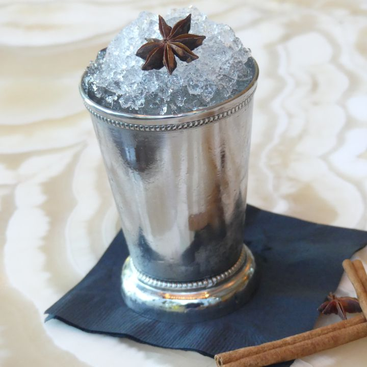 A silver Julep cup rests on a black bar napkin on a wavy marble bar top. The cup is filled with crushed ice and topped with a single intact star anise.