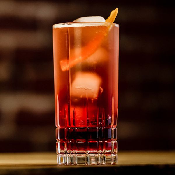 americano cocktail in a tall glass with an orange peel garnish
