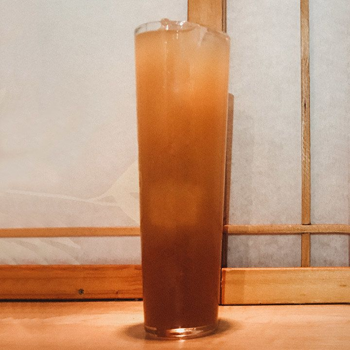 A tall, narrow glass is filled with a few ice cubes and a cloudy red-brown drink. Behind the glass is a paper window with wood frames.