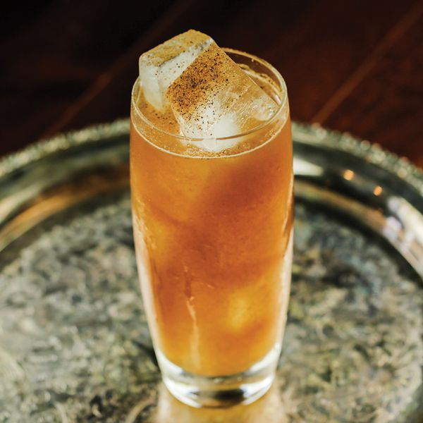 A tall, gently tapered highball glass sits on a silver bar tray, which rests on hardwood. The glass is filled with a brown highball drink and a number of large ice cubes, with a gentle dusting of nutmeg on top.