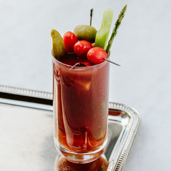 Bloody Bulldog cocktail in a highball glass, loaded with garnishes (tomatoes on a skewer, pickles, olive, asparagus), served on a silver tray