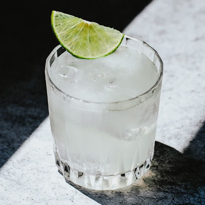 Golden Glove cocktail in a rocks glass with a half lime wheel, served in a sunbeam on a white textured surface