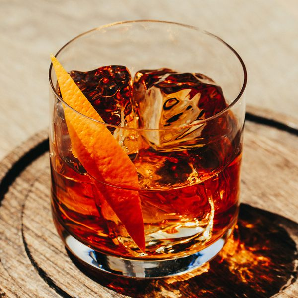 A rocks glass with wide-set, thin, unembellished walls holds three large ice cubes, a dark red whiskey drink, and a thin orange peel. It sits on a round wooden surface.