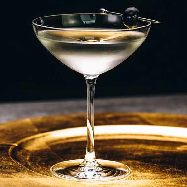 A crystal-clear Martini in a coupe glass garnished with a brandied cherry on a pick