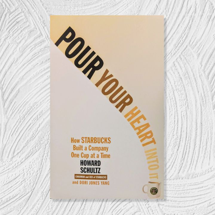 Pour Your Heart Into It cover, coffee-colored gradient background and text with a curved vertical title leading into a Starbucks mug